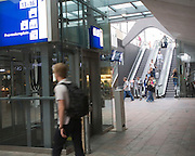 People in the concourse of Rotterdam Central railway station, Netherlands with escalator descending from platform.