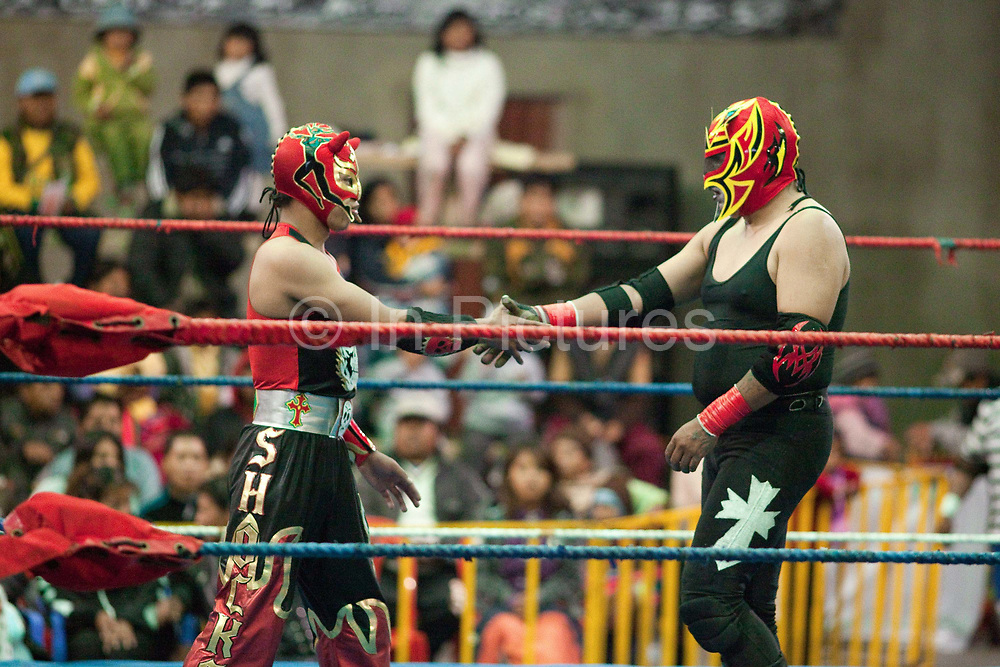 Male wrestlers in ring shaking hands. Lucha Libre wrestling origniated in Mexico, but is popular in other latin Amercian countries, including in La Paz / El Alto, Bolivia. Male and female fighters participate in the theatrical staged fights to an adoring crowd of locals and foreigners alike.
