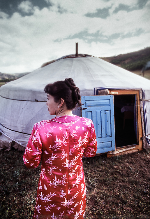 Detail of a pink Mongolian dress on a young woman in front of a yurt.