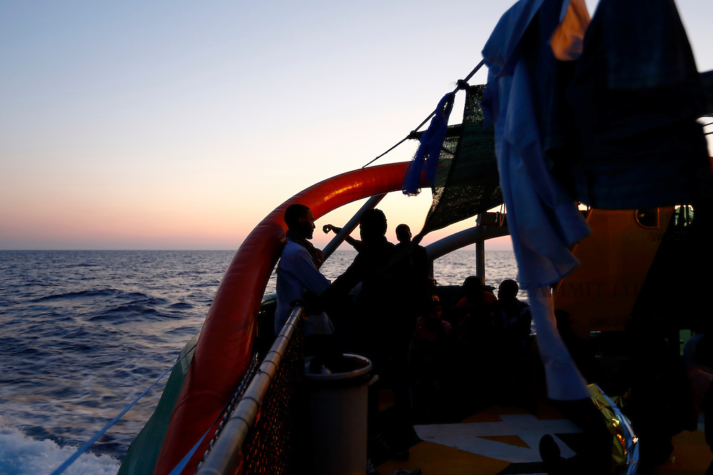 Migrants rest on the deck of the Medecins san Frontiere (MSF) ship Bourbon Argos off the coast of Libya at sunset August 7, 2015.  Some 241 mostly West African migrants on the ship are expected to arrive on the Italian island of Sicily on Sunday, according to MSF.<br /> REUTERS/Darrin Zammit Lupi <br /> MALTA OUT. NO COMMERCIAL OR EDITORIAL SALES IN MALTA