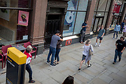 As other passers-by pedestrians walk past, a man and woman kiss on the Strand, on 11th July, in London, England.