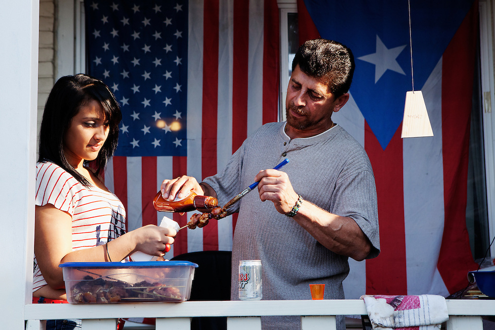 """BETHLEHEM, PA – JUNE 19, 2011: Aeri Rosto (right), 53, grills hot dogs and kabobs to celebrate Father's Day outside the home of Eugenia Rivera, a Hispanic South Side Bethlehem resident. Rosto has lived the U.S. for 32 years. """"My father was a cook,"""" he said. """"I started cooking with him when I was eight years old. I love it here. I have my 3 kids, my grandson. It's a great place to live.""""<br /> Although Rosto lives in Bethlehem, he works in Somerville, New Jersey to support his family, commuting 45 minutes to work each day.<br /> <br /> As the population of second and third generation Hispanics increases dramatically in the United States, a new boldness can be sensed among Latinos in America, stretching far beyond the southern border states. Demographers in Pennsylvania say the towns of Bethlehem, Allentown and Reading are set to become majority-minority cities, where Hispanics comprise a bigger portion of the population than whites. As this minority population increases dramatically in the region, Latinos are inching closer to their own realization of the American Dream, while gradually shifting the physical and cultural landscapes of their communities."""
