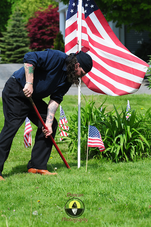 """BATH -- 5/25/15 - Richard Harvey of Wiscasset prepares the area around the Library Park Memorial before Memorial Day ceremonies on Monday. Harvey, who is not a veteran himself, honors those who served and fell as part of the """"We Remember Committee."""" He works to keep the memories of fallen service members alive. <br /> The Memorial Day Parade in Bath took place as a result of an anonymous donor who gave $5,000 and the American Legion who donated $3,000 to pay for the parade in Bath. The Elks Club supported the parade in prior years but were unable to do so this year, leaving organizers without a funding source close to the parade date.  <br /> Photo ©2015 by Roger S. Duncan / For the Forecaster."""