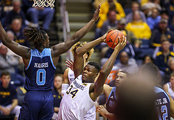 Dec 1, 2019; Morgantown, WV, USA; West Virginia Mountaineers forward Oscar Tshiebwe (34) makes a move in the lane while defended by Rhode Island Rams forward Jermaine Harris (0) during the second half at WVU Coliseum. Mandatory Credit: Ben Queen-USA TODAY Sports