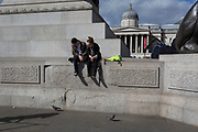A young couple sitting on the plinth of Nelson's Column in Trafalgar Square, watch one of two pigeons on 21st March 2017, in London, England.