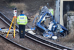 © Licensed to London News Pictures. 17/02/2018. Horsham, UK. A policeman stands next to the remains of a car near a level crossing after two people were killed near the village of Barns Green. Photo credit: Peter Macdiarmid/LNP