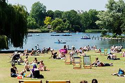 © Licensed to London News Pictures. 06/07/2013. London, UK.  Londoners enjoy the sunny weather in Regents Park, central london, amongst deck chairs alongside the boating lake.  Photo credit : Richard Isaac/LNP
