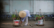 A vietnamese woman sells flowers in a street of Hoi An, Vietnam, Asia. Une femme vietnamienne vends des fleurs dans une rue de Hoi An.