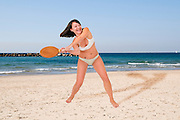 Young woman in a bikini plays racquetball on the beach