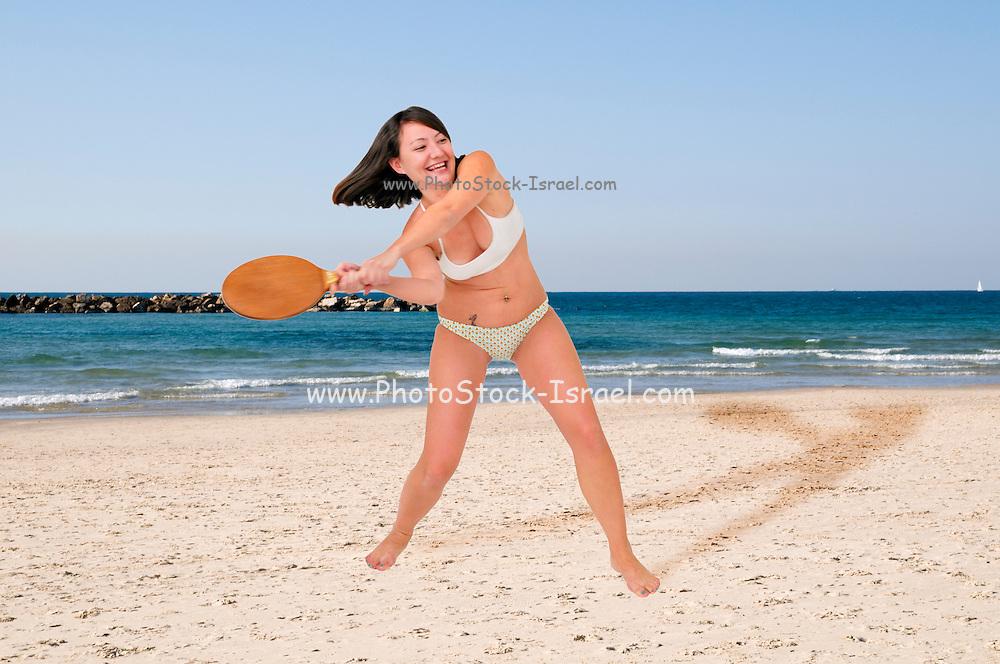 Young woman in a bikini plays racquetball on the beach
