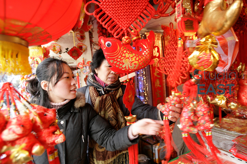 SHANGHAI, CHINA - January 08: Two women browse decorations for the upcoming Chinese New Year on January 8, 2009 in Shanghai, China. (Photo by Lucas Schifres/Getty Images)