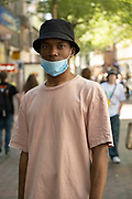 Young man wearing a face mask happy to be out and about as the coronavirus restrictions continue and the government is about to announce an extension to the original freedom day planned for June, slowing the process of easing, more and more people begin to come to the city centre, seen here on New Street on 15th June 2021 in Birmingham, United Kingdom. After months of lockdown, the first signs that life will start to get back to normal continue, with more people enjoying the company of others in public, while uncertainty continues for a projected further month, which is being dubbed The final push.