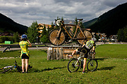 Cyclists rest by a large wooden mountain bike sculpture in the town of Corvara during the summer walking season in south Tyrol, northern Italy. Corvara is the main center of Alta Badia, a prestigious tourist area located at the top end of the Val Badia, surrounded by the peaks of the Dolomites mountains. Corvara (German: Corvara or Kurfar; Italian: Corvara in Badia) is a comune (municipality) in South Tyrol in northern Italy, located about 40 kilometres (25 mi) east of Bolzano.