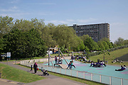 Burgess Park playgorund with the Aylesbury Estate, a large housing estate located in Walworth, on the horizon on 13th May 2016 in South London, United Kingdom. The Aylesbury Estate contains 2,704 dwellings and was built between 1963 and 1977. The estate is partially occupied and is currently undergoing a major redevelopment.
