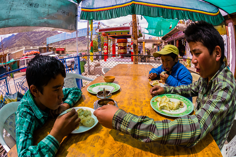Boys eating lunch at a restaurant in Karu, Leh Valley, Ladakh, Jammu and Kashmir State, India.