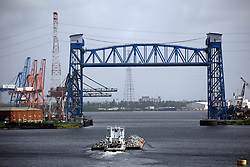 29 August 2006. New Orleans, Louisiana. Lower 9th ward. A tug boat moves a barge full of scrap metal up the Industrial Canal. The levee wall (to the rt out of frame) burst during hurricane Katrina, swamping the Lower 9th ward, killing hundreds of victims.<br /> Photo Credit©; Charlie Varley/varleypix.com