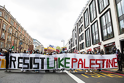 London, UK. 15th May, 2021. Activists walk behind a Resist Like Palestine banner as hundreds of people take part in a Free Palestine SOS Colombia solidarity rally and march from the Colombian embassy to the Israeli Embassy. Speakers highlighted human rights abuses such as forced displacement being directed against Palestinians in Israel and the Occupied Territories and the killing, repression, detention and torture of peaceful demonstrators and human rights defenders in Colombia.