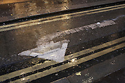 Left-turn traffic arrow and double-yellow no parking lines shine during rain on a wet street in London's West End.