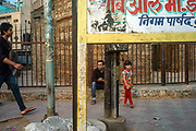 A child and her father wait near the Kashmere Gate, Old Delhi, India.