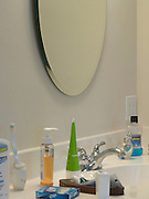 detail of mirror with faucet and various toiletry