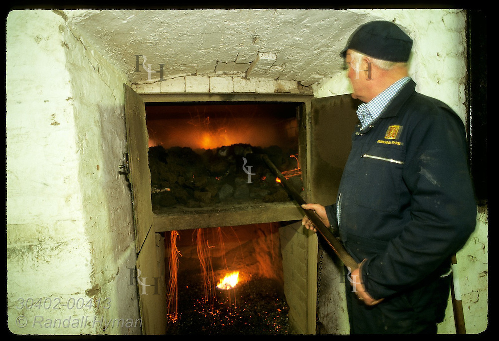 Worker stokes peat fire of kiln as barley roasts at Highland Park Distillery; Orkney Islands. Scotland