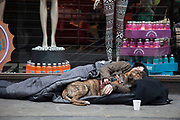 Homeless man beds down in his sleeping bag with his dog as companion on a busy Oxford Street in London, amidst the bustle of passers by. This is one of the busiest junctions in London, so whilst it is an odd and noisy place to sleep, he has some liklihood of making some money too.