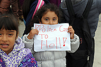 A young girl holds a sign expressing the general sentiment on Wednesday afternoon at the scene of Tuesday's officer-involved shooting near the Sanborn Plaza Market at the corner of Del Monte Avenue and North Sanborn Road in Salinas.