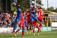 AFC Wimbledon defender Deji Oshilaja (4) battles for header in the box during the EFL Sky Bet League 1 match between AFC Wimbledon and Scunthorpe United at the Cherry Red Records Stadium, Kingston, England on 15 September 2018.