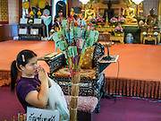 """13 MAY 2013 - BANGKOK, THAILAND: A woman prays after making an offering during Vesak ceremonies at Wat That Thong in Bangkok. Vesak, called Wisakha Bucha in Thailand, is one of the most important Buddhist holy days celebrated in Thailand. Sometimes called """"Buddha's Birthday"""", it actually marks the birth, enlightenment (nirvana), and death (Parinirvana) of Gautama Buddha in the Theravada or southern tradition. It is also celebrated in Cambodia, Laos, Myanmar, Sri Lanka and other countries where Theravada Buddhism is the dominant form of Buddhism.     PHOTO BY JACK KURTZ"""