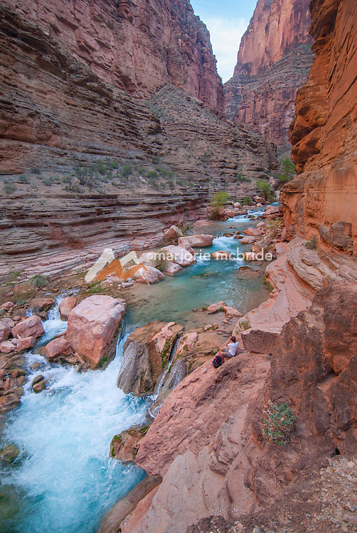 Male taking pictures sitting along the edge of Havasu Creek Canyon on the Colorado River  in the Grand Canyon National Park, Arizona.