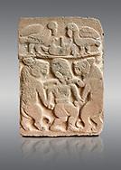 Pictures & images of the North Gate Hittite sculpture stele depicting man with wolves. 8the century BC.  Karatepe Aslantas Open-Air Museum (Karatepe-Aslantaş Açık Hava Müzesi), Osmaniye Province, Turkey. Against grey background