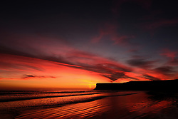 © Licensed to London News Pictures. <br /> 26/03/20167. <br /> Saltburn by the Sea, UK.  <br /> <br /> A spectacular sunrise starts the day over Huntcliff and the beach in Saltburn by the Sea.<br /> <br /> Photo credit: Ian Forsyth/LNP