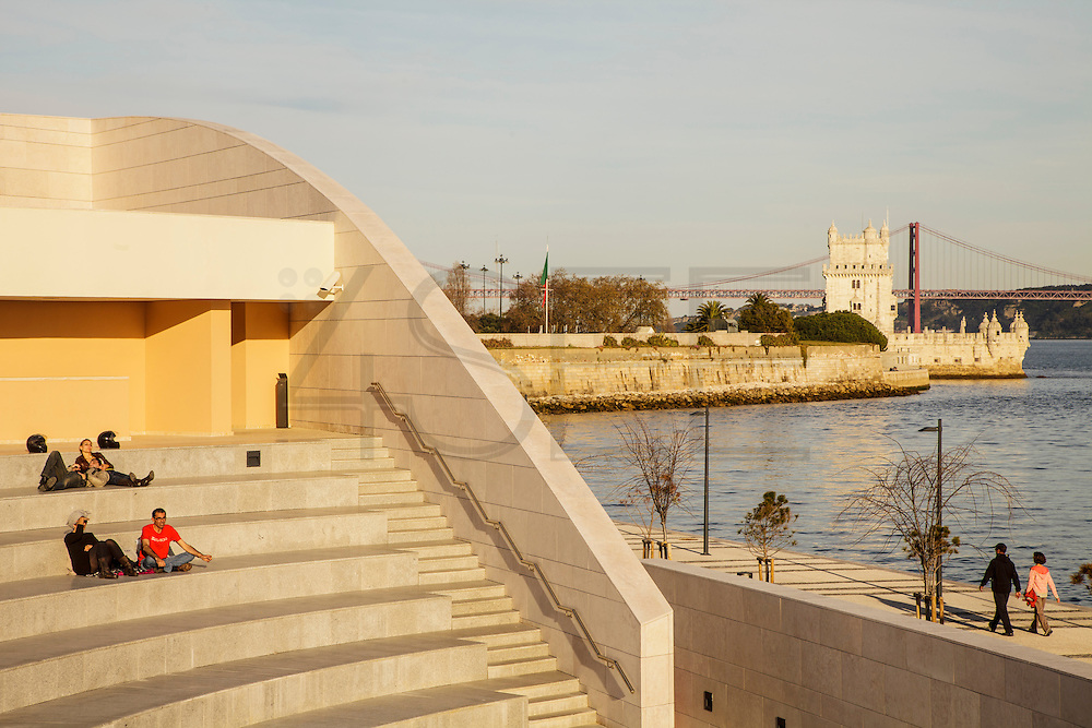People enjoying the sunset at Champalimaud Centre for the Unknown's open-air auditorium. At the distance Belém Tower and 25th of April bridge can be seen. The Champalimaud Foundation's high-tech research center, which opened in 2010 at the mouth of the River Tagus in Lisbon, features diagnostic and treatment units for cancer patients on the lower floors and research labs above, aimed at research on cancer and neuroscience.