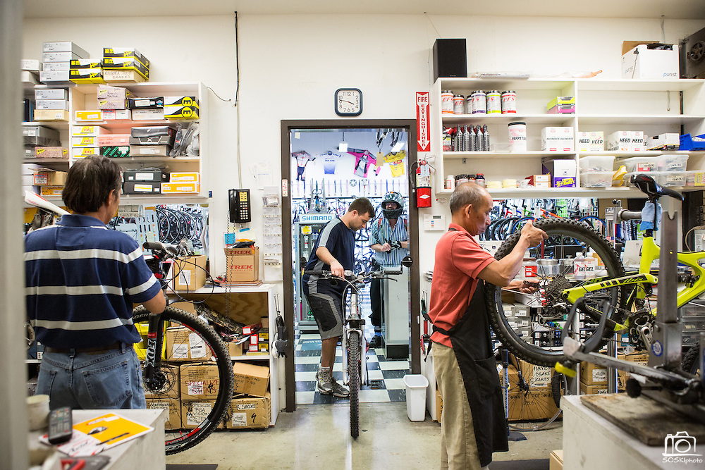Associate Francis Landice brings a customer's damaged bike into the repair shop of Sun Bike Shop in Milpitas, Calif., for inspection, while mechanics Peter Nguyen (left) and Jason Tran (right) are routing new brake cables and replacing damaged wheels on Sept. 18, 2012.  Photo by Stan Olszewski/SOSKIphoto.