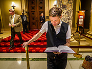 01 MAY 2017 - ST. PAUL, MN: JOHAN GALOO, who said he is running for mayor of Minneapolis, reads the bible in front of the Minnesota State Senate Chamber in the state capitol. About 300 people, representing immigrants' and workers' rights organizations, marched through the Minnesota State Capitol during a demonstration to mark May Day, International Workers' Day.      PHOTO BY JACK KURTZ