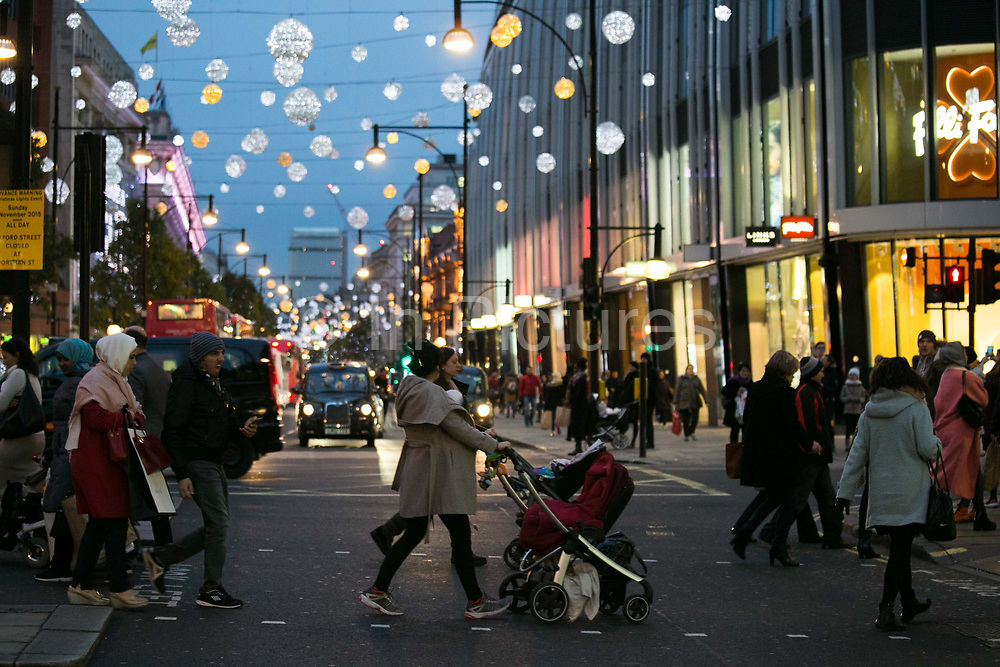 Pedestrians with buggies cross Oxford Street at dusk 20th November 2015. Nitrogen Oxide NOx pollution in London is a big killer and London is one of the worst affected in Europe. Babies in buggies are the most exposed to the fumes.