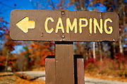 A sign points to a campground against fall foliage