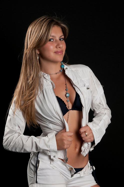 Young hispanic girl posing very sexy and smiling.