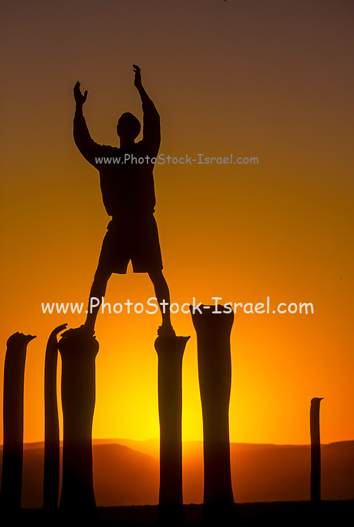 Silhouette of a boy standing on piles with the setting sun behind him