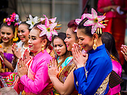 "29 APRIL 2017 - MINNEAPOLIS, MINNESOTA: Thai women ""wai"" (a traditional Thai greeting) during New Year greetings at Songkran Uptown in Minneapolis. Several thousand people attended Songkran Uptown on Hennepin Ave in Minneapolis for the city's first celebration of Songkran, the traditional Thai New Year. Events included a Thai parade, a performance of the Ramakien (the Thai version of the Indian Ramayana), a ""Ladyboy"" (drag queen) show, and Thai street food.     PHOTO BY JACK KURTZ"