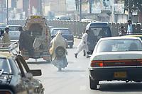 19 OCT 2001, RAWALPINDI/PAKISTAN:<br /> Mopedfahrer zwischen Autos im Abgasdunst auf einer Hauptstrasse von Rawalpindi in der Naehe von Islamabad<br /> IMAGE: 20011019-02-006<br /> KEYWORDS: Motorrad, Motorradfahrer, motorbike, smoke, Abgas, Umwelt, environment