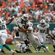 Jets quarterback Mark Sanchez (6)gets hit as he releases the ball during an NFL football game between the New York Jets and the Miami Dolphins on Sunday, September 23, 2012 at SunLife Stadium in Miami, Florida. (AP Photo/Alex Menendez)