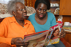 Daughter and mother looking at magazine.