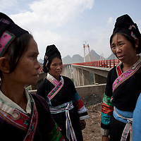 """There is no word for tunnel in the Buyi language. Lu Deqing calls it """"the long cave."""" Lu, at left, is dressed in her finest as she and the other village ladies visit the entrance where the tunnel meets the bridge platform. They are proud of the bridge and the fact that it spans over their valley. They sing songs praising its beauty and hope the bridge will bring some good to their lives. <br /> <br /> Private investors have already contacted bridge engineer Zhou. They want to invest 70 to 80 million yuan to develop the Baling River valley. Their plans include building a luxury hotel, theme park and a glass restaurant with river views. Activities will include paragliding and bungee jumping. Tourists will want to see the local minorities and have them sing and dance for their entertainment, wearing satin and sequined parodies of their traditional clothing."""