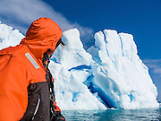 A blue iceberg juts from the Southern Ocean at Graham Land, in Antarctica. A man in orange coat looks on.