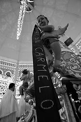 Un putto fotografato affianco alla statua della Santa protettrice di Mesagne (Br), la Madonna del Carmine.  Come ogni anno il 15, 16 e 17 di luglio si celebra la ricorrenza in onore della vergine che salvò la popolazione da un terribile terremoto avvenuto nel 1700 circa. La foto è stata scattata il 15 luglio 2010.