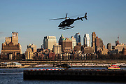 A silhouetted helicopter comes into land in the Downtown Manhattan/ Wall Street Heliport; Pier 6, Manhattan, New York City, New York, United States of America. Another helicopter waits on the helipad. Brooklyn borough can be seen in the background.