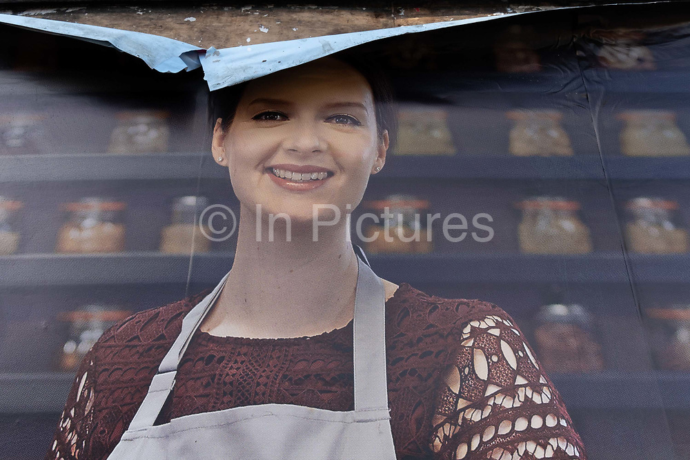 The layers of advertising sheets are peeling away above the head of a female model advertising a retail brand on a billboard in Surbiton, on 12th November 2020, in London, England.