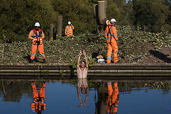 HS2 security guards monitor an anti-HS2 activist swimming in the Grand Union Canal to halt tree felling works alongside HOAC lake in connection with the HS2 high-speed rail link on 21 September 2020 in Harefield, United Kingdom. Anti-HS2 activists continue to try to prevent or delay works for the controversial £106bn HS2 high-speed rail link on environmental and cost grounds from a series of protection camps based along the route of the line between London and Birmingham.