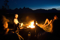 A group of friends relax around a campfire in Jackson Hole, Wyoming.